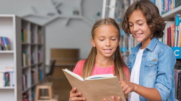 Bambini che leggono da un libro con copia spazio Foto Gratuite