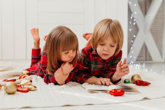Bambini che leggono insieme il giorno di natale Foto Gratuite