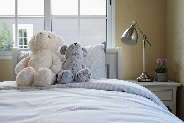 Kids room with dolls and pillows on bed and bedside table lamp Premium Photo