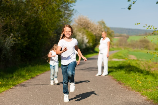 Kids running down a path, pregnant mother standing Premium Photo
