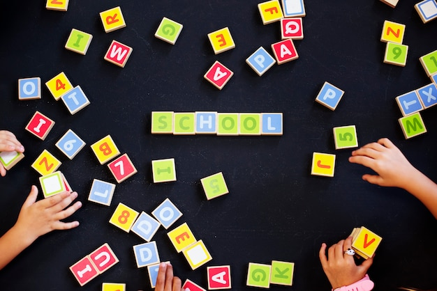 Kids spelling out words with alphabet blocks Premium Photo