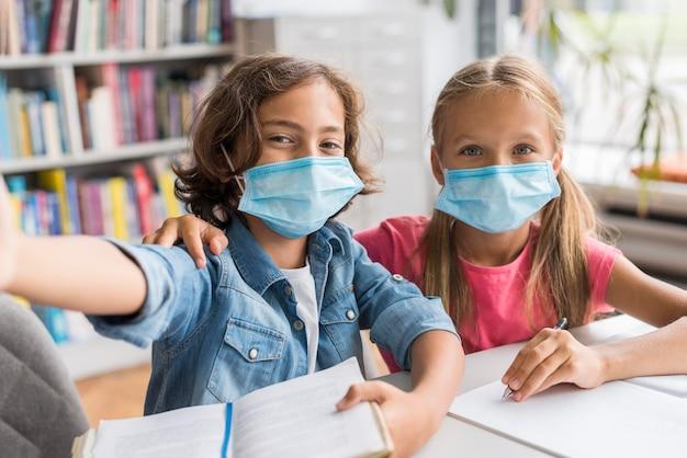 의료 마스크를 쓰고 도서관에서 셀카를 찍는 아이들 무료 사진