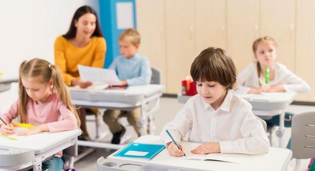 Дети делают заметки в классе Premium Фотографии