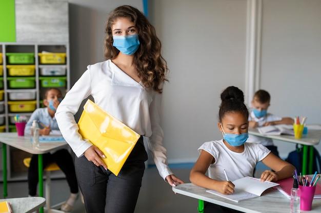 Bambini e insegnante che si proteggono con maschere mediche Foto Gratuite