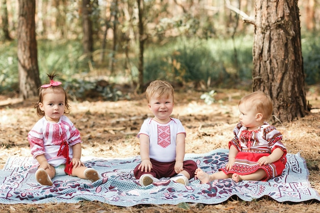 Kids in traditional ukrainian clothes play in forest in sunbeam. boy and two girls Free Photo