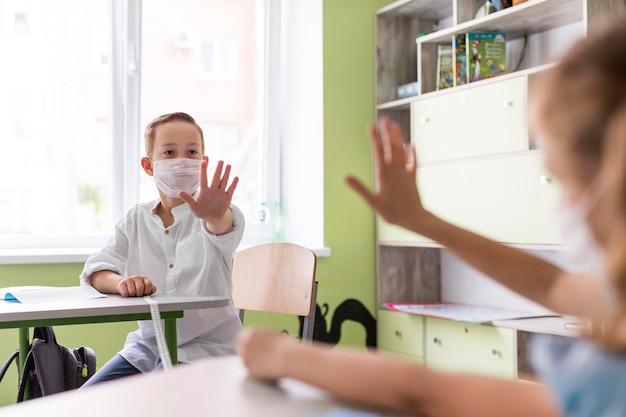 Bambini che salutano in classe mantenendo la distanza sociale Foto Gratuite