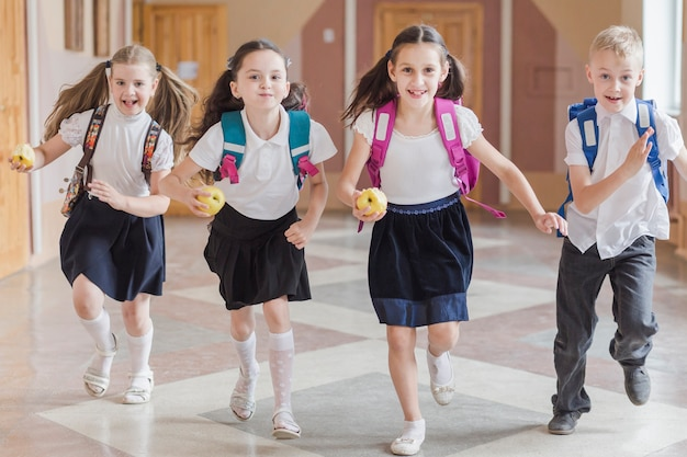 Kids with apples running on school corridor Free Photo