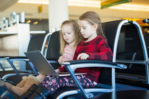 Kids with a laptop at the airport while waiting his flight Premium Photo