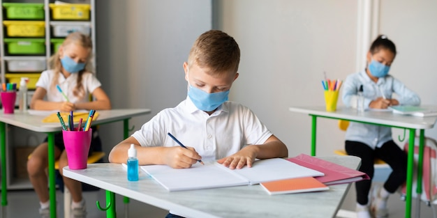 Kids writing in classroom while wearing medical masks Free Photo
