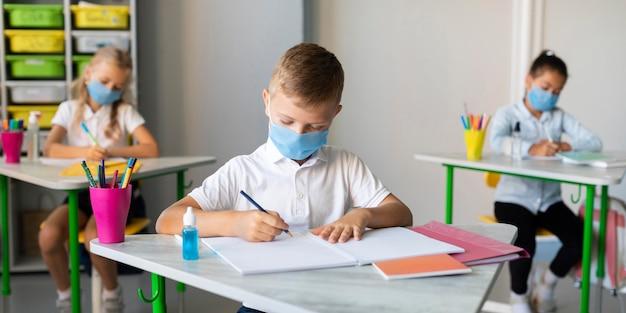 Дети пишут в классе в медицинских масках Бесплатные Фотографии