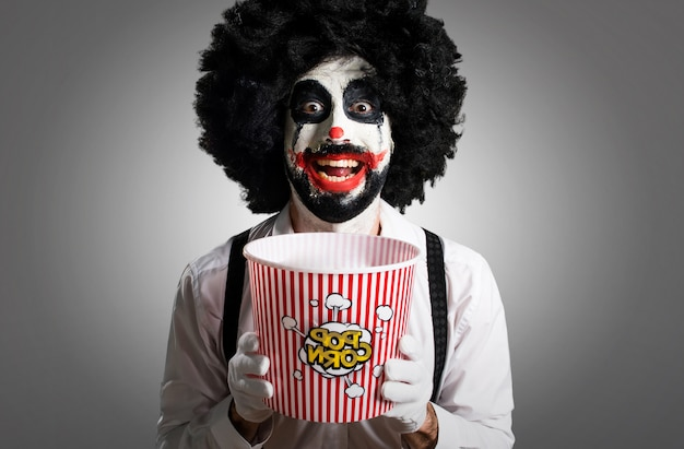 Killer clown eating popcorns on textured background Premium Photo