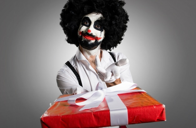 Killer clown holding a gift on textured background Premium Photo