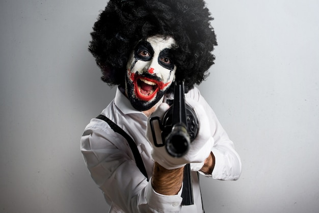 Killer clown holding a rifle on textured background Premium Photo