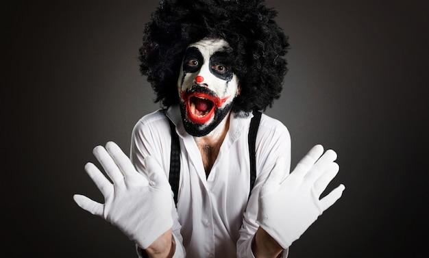 Killer clown making surprise gesture on textured background Premium Photo