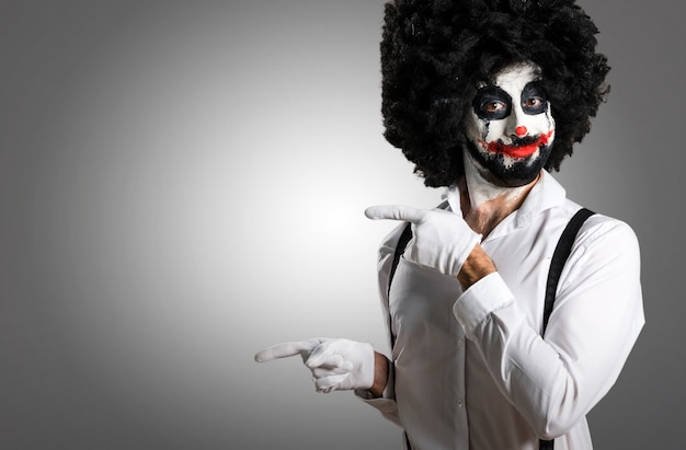 Killer clown pointing to the lateral on textured background Premium Photo