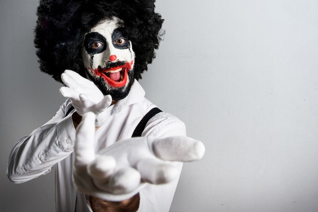 Killer clown presenting something on textured background Premium Photo