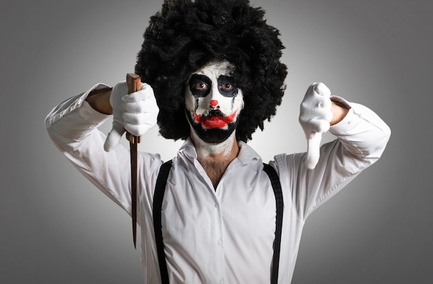 Killer clown with knife making bad signal on textured background Premium Photo