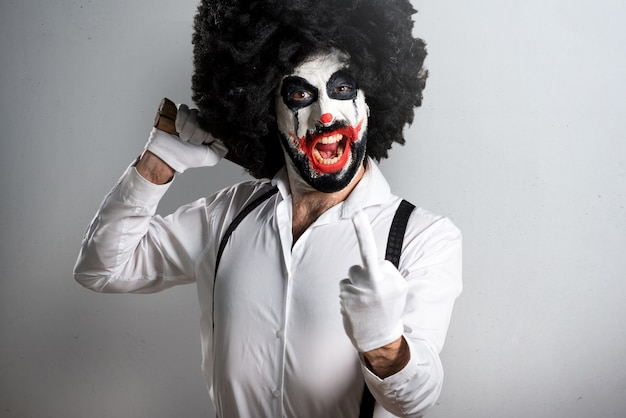 Killer clown with knife making horn gesture on textured backgrou Premium Photo