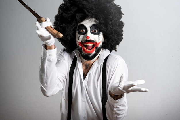 Killer clown with knife making surprise gesture on textured back Premium Photo