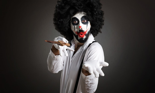 Killer clown with knife presenting something on textured backgro Premium Photo