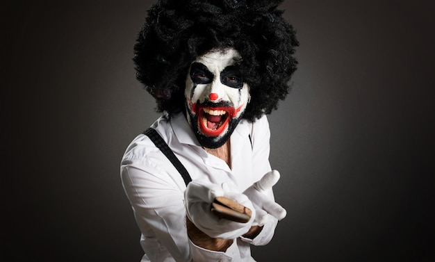 Killer clown with knife shouting on textured background Premium Photo