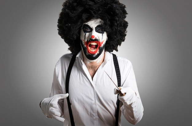 Killer clown with knife on textured background Premium Photo