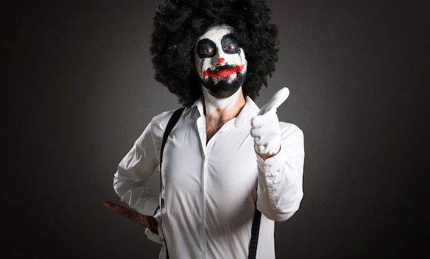 Killer clown with knife with thumb up on textured background Premium Photo