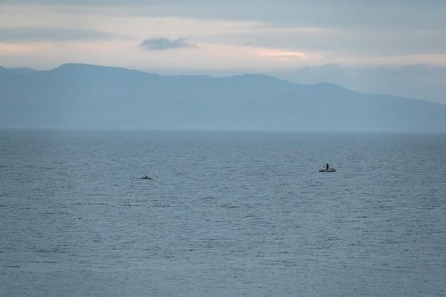 漁師のボートの近くでシャチが泳ぐ Premium写真