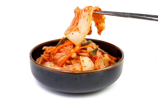 흰색 배경, 평면도에 젓가락으로 그릇에 김치 양배추. 프리미엄 사진
