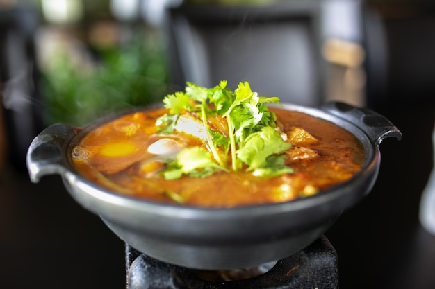 Kimchi soup with raw chicken eggs and white tofu, popular korean food. Premium Photo