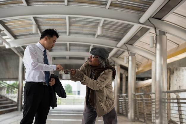 Kind businessman give money to beggar Premium Photo