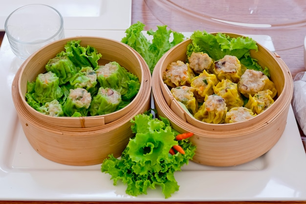 Kind of chinese snacks, chinese steamed dimsum in bamboo with green and yellow colors. Premium Photo