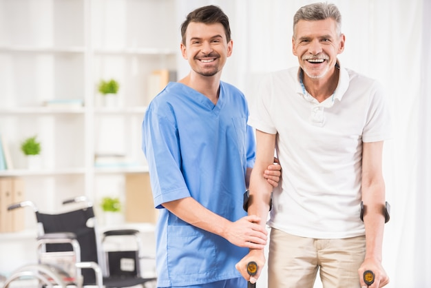 Kind male nurse helping senior patient on crutches. Premium Photo