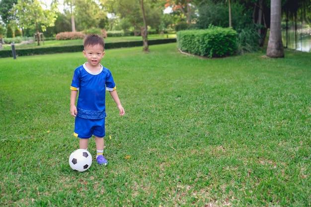 Kindergarten boy in soccer uniform is playing football Premium Photo