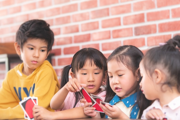 Kindergarten children playing with counting card in class room Premium Photo