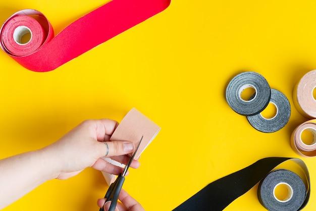 운동 요법 테이핑 처리 공정 단계. 여성의 손은 노란색의 적용을 위해 빨간 테이프를 자르고 있습니다. 프리미엄 사진