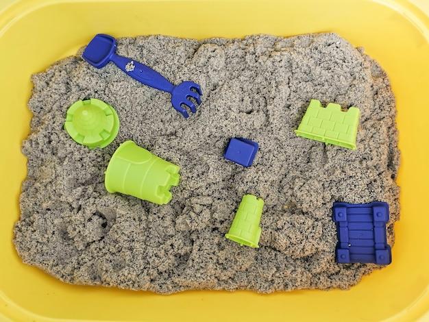 노란색 용기에 장난감이 담긴 자연스러운 색의 운동 모래. 훌륭한 운동 능력을위한 아이들과 함께하는 교육용 게임. 프리미엄 사진