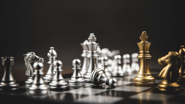 King golden chess standing confront of the silver chess team. Premium Photo