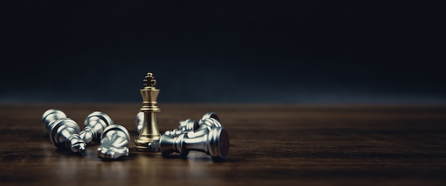King golden chess standing in the middle of the falling silver chess. Premium Photo