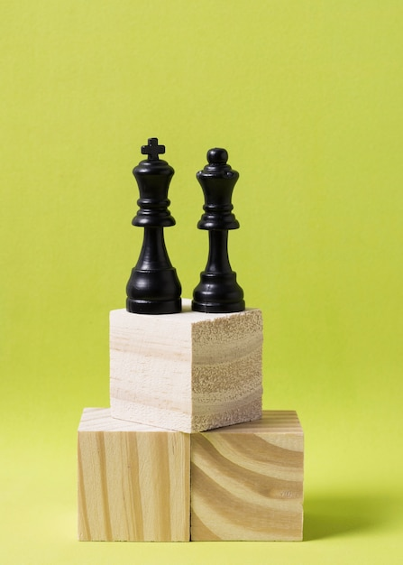 King and queen pieces of chess on wooden cubes at same height Free Photo