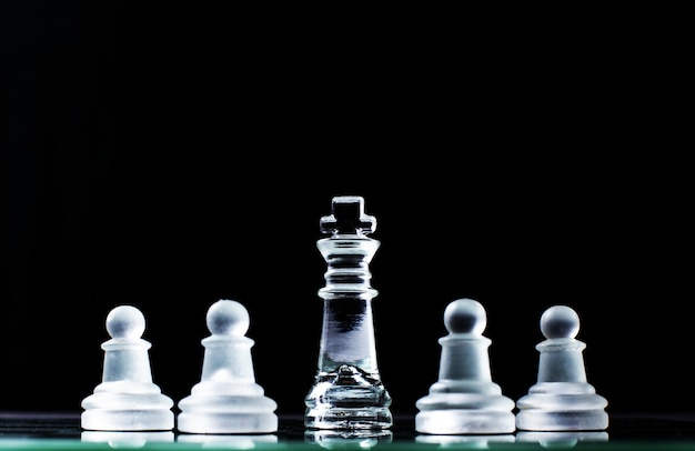 King and several pawns on chessboard in dark background. hierarchy concept. Free Photo