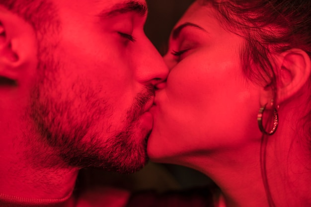 Kiss of young guy and attractive lady in redness Free Photo