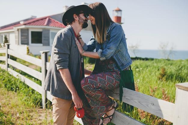 田舎、自由奔放に生きる夏のファッションで歩いて恋に幸せな若いスタイリッシュな流行に敏感なカップルのキス 無料写真