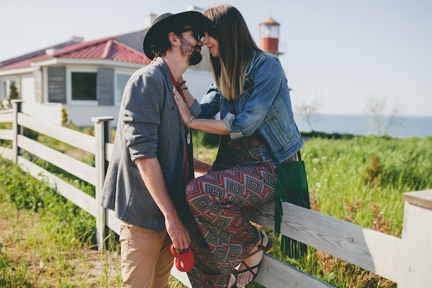 Kissing happy young stylish hipster couple in love walking in countryside, summer style boho fashion Free Photo
