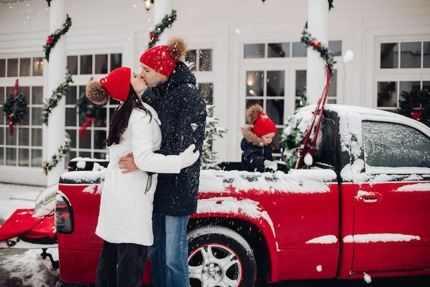 Baciare i genitori in cappelli rossi sotto la nevicata all'aperto Foto Gratuite