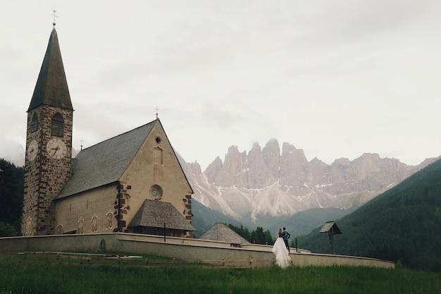 Kissing wedding couple stands before stone church in mountains Free Photo