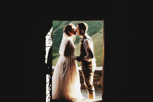 Kissing wedding couple stands in the doors before beautiful mountains in georgia Premium Photo