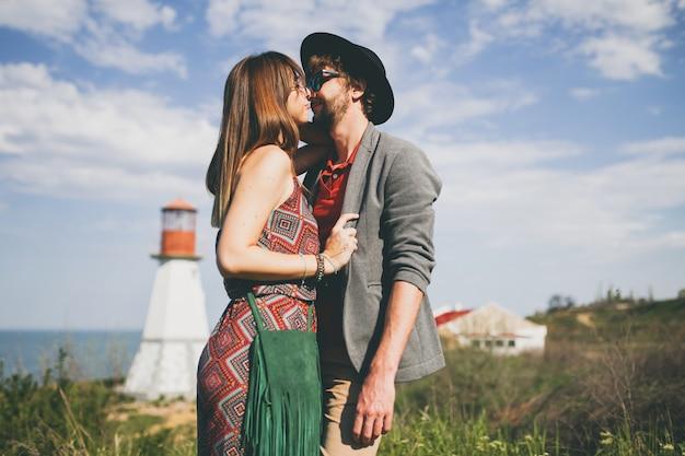 Baciare lo stile indie delle coppie giovani hipster nell'amore che cammina nella campagna, faro sullo sfondo Foto Gratuite