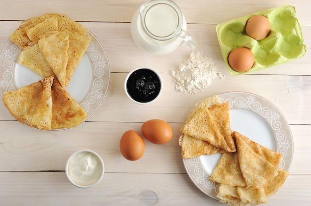 A kit for making pancakes, eggs, milk, pitcher, flour, sour cream and jam Premium Photo