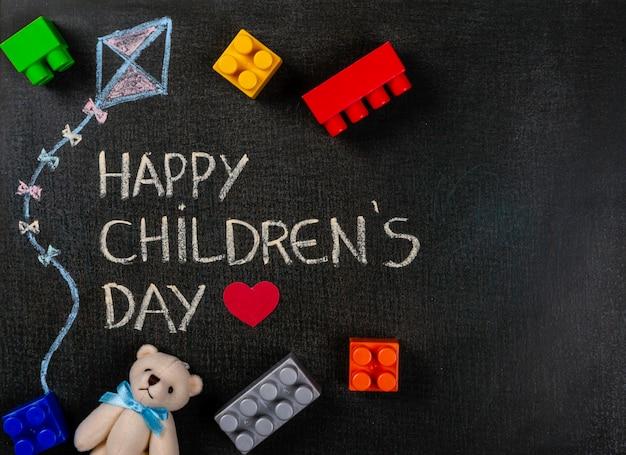 ハッピー子供の日と散らばった台紙とテディベアと漫画kitを書かれた黒板 Premium写真
